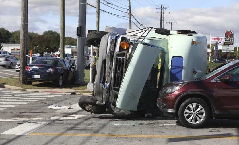Sylvania Township fire and police crews respond to a multiple vehicle crash involving a bus, Friday, Oct. 4, 2019, in Sylvania Township, near Toledo, Ohio. Authorities say the bus carrying developmentally disabled people flipped over during the crash and sent 13 people to hospitals. (Lori King/The Blade via AP)