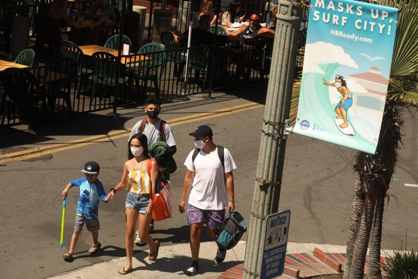 Richard Hernandes, Jazmin Domingo, his brothers Seth Patlan, 5, and Joseph Hamassian in Huntington Beach on Aug. 12.