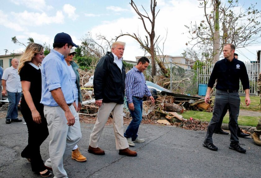 U.S. President Donald Trump walks past hurricane wreckage as he participates in a walking tour with first lady Melania Trump, Guaynabo Mayor Angel Perez Otero (second right) and Acting FEMA Administrator Brock Long (far right) as well as Puerto Rico Governor Ricardo Rossello (left) and his wife Beatriz Areizeaga in areas damaged by Hurricane Maria in Guaynabo, Puerto Rico, U.S., Oct. 3, 2017.