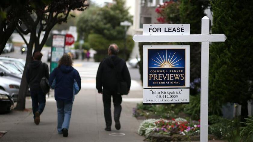 Peatones caminan frente a un letrero de renta de propiedad en San Francisco.