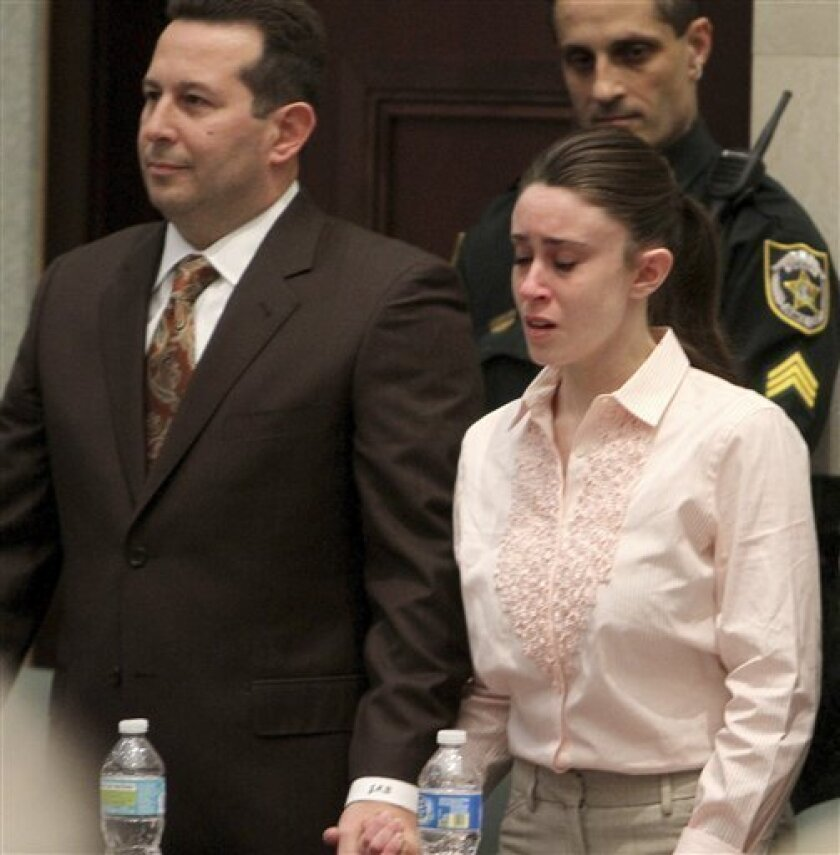 FILE - In this July 5, 2011 file photo, Casey Anthony holds hands with her defense attorney Jose Baez as they listen to the verdict at the Orange County Courthouse in Orlando, Fla. Baez was a little known attorney with not much experience, a high school dropout who turned his life around after a stint in the Navy. He took on one of the nation's highest profile murder cases and won it against all odds. His defense strategy was roundly criticized by experts, but with hindsight some are calling it brilliant. (AP Photo/Red Huber, Pool, File)