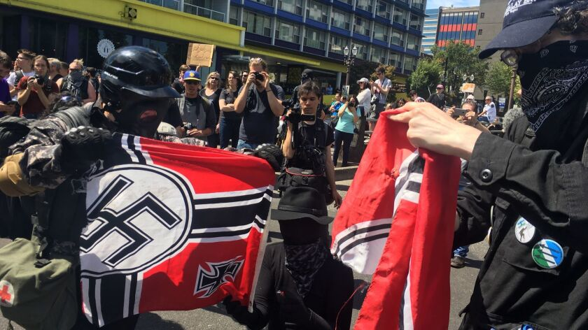 Counter-protesters tear a Nazi flag Saturday, at a rally in Portland, Ore., by far-right demonstrators.