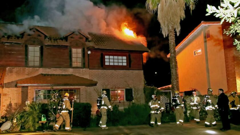 Burbank firefighters work to put out a house fire on the 1600 block of Oak Street in Burbank Monday night.