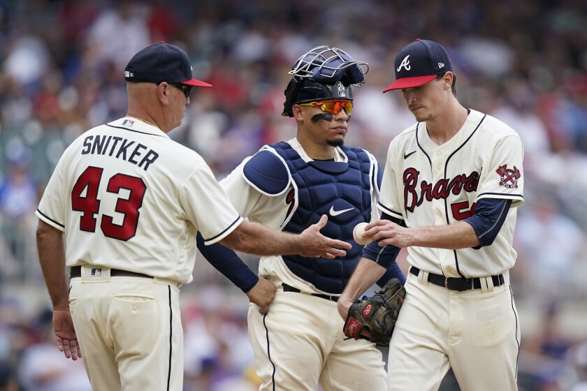 Atlanta Braves starting pitcher Max Fried, right, hands the ball over to Atlanta Braves manager Brian Snitker, left, as catcher William Contreras, center, looks on in the seventh inning of a baseball game against the Los Angeles Dodgers Sunday, June 6, 2021, in Atlanta. (AP Photo/Brynn Anderson)