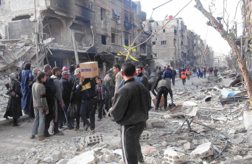 Residents of Syria's besieged Yarmouk Palestinian refugee camp, south of Damascus, wait to receive food parcels last month.