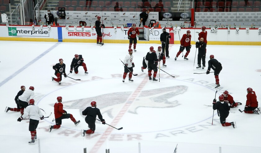 Arizona Coyotes players and coaches pause on the ice during practice in Glendale, Ariz.