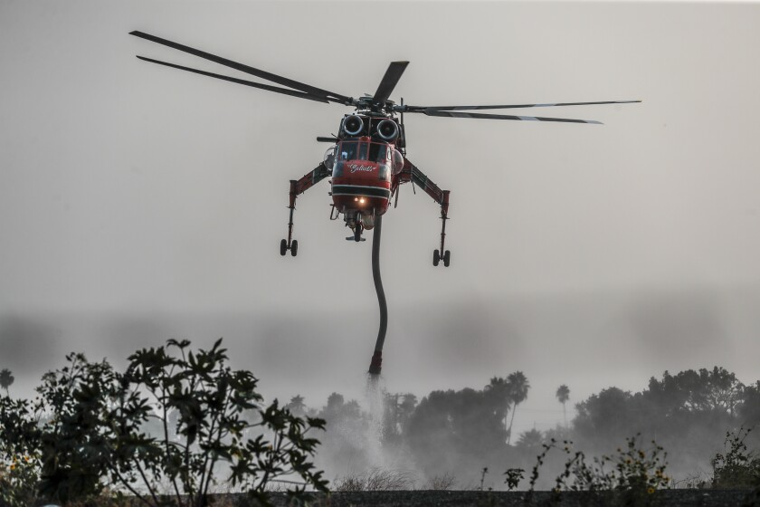 A fire fighting helicopter refills in a reservoir on Grand View Ave. as crews continue to battle the Bobcat fire