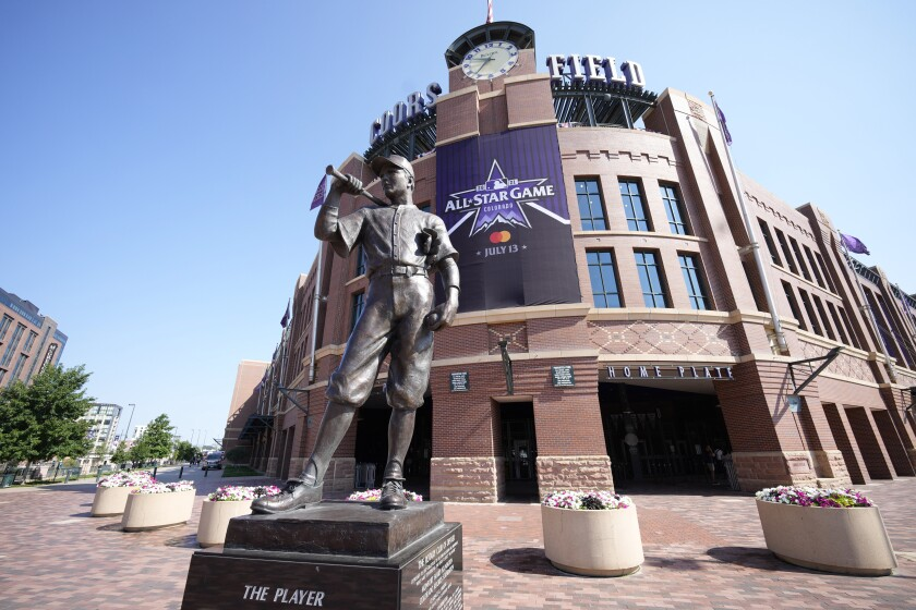 """An All-Star Game banner hangs from the front entrance of Coors Field behind """"The Player"""" sculpture."""