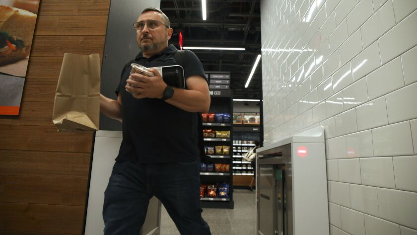 Peter Feldman, black shirt, walks out with his purchases at the new Amazon Go store on the 100 block