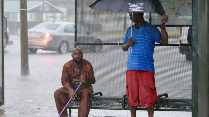 Residents sit under a bus shelter along a flooded Broad Street as heavy rain falls, Wednesday, July