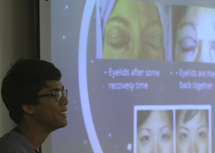 Rom Chaiprasert shows images from an eyelid restoration surgery during his exit interview at Murrieta Mesa High School on Thursday. This year, for the first time, the school district is requiring that students successfully complete an exit interview before they receive their diploma.