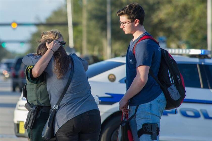 Una oficial de policía consuela a una mujer tras el tiroteo registrado hoy, miércoles 14 de febrero de 2018, en la escuela secundaria Marjory Stoneman Douglas de la ciudad de Parkland, en el sureste de Florida (Estados Unidos). EFE