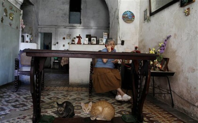 Margarita Alonso speaks on the phone as her cats sit under a table inside her home in Old Havana, Cuba, Wednesday Feb. 1, 2012. (AP Photo/Javier Galeano)
