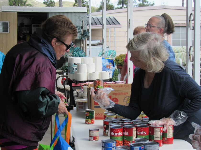 Volunteer Darla McCarver (right) helps shopper Carol Russo (left) find out the ingredients in one of the items she is interested in taking at a shopping event for seniors on Sunday, March 29, inside the Meadowbrook Mobile Home Park in Santee. The park puts out food a few times a week so that residents can get some of their groceries without venturing out.