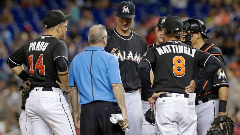 The Marlins' Colin Rea, third from left, talks manager Don Mattingly (8) in the fourth inning of a baseball game against the St. Louis Cardinals, Saturday, July 30, 2016, in Miami.