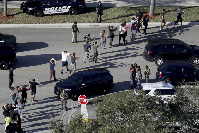 Students hold their hands in the air as they are evacuated by police from Marjory Stoneman Douglas H