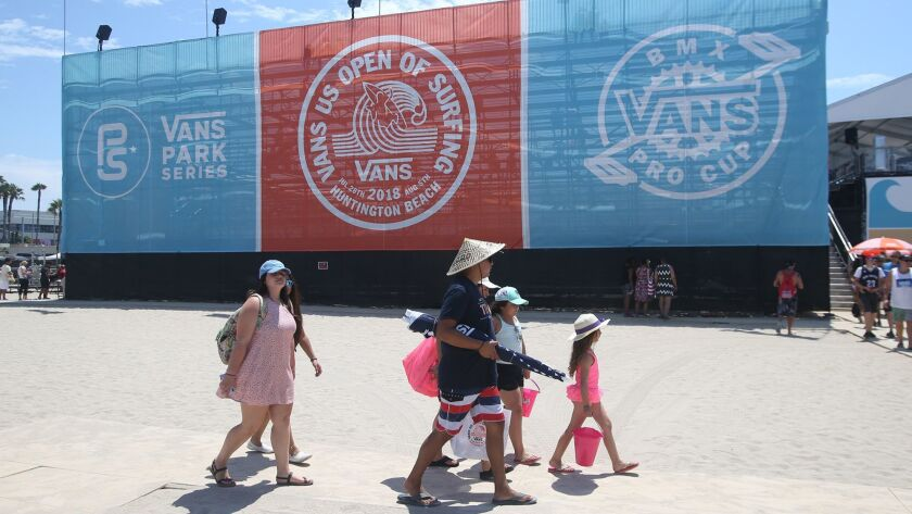 A family walk past the grandstands in the during the Van's US Open of Surfing on Tuesday.
