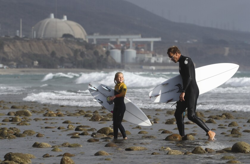 A pair of surfers exit the water at San Onofre State Beach