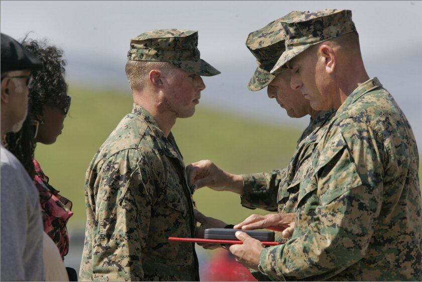 Navy petty Officer 3rd. Class Peter A. Gould has a Silver Star Medal pinned on him by Marine Lt. Col. Fridrik Fridriksson for heroism in Afganistan. At far right is Marine Sgt. Major Scott Samuels. At left in sunglasses is Stacia Harris, wife of Marine Cpl. Larry D. Harris Jr. who received the Silver Star Medal posthumously for for the same incident. At far left is Bruce Merriweather, the father of Larry D. Harris.