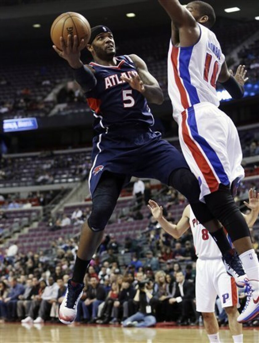 Atlanta Hawks forward Josh Smith (5) shoots around Detroit Pistons center Greg Monroe (10) during the first quarter of an NBA basketball game at the Palace in Auburn Hills, Mich., Monday, Feb. 25, 2013. (AP Photo/Carlos Osorio)