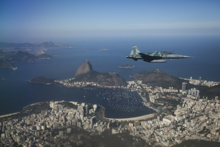 A F-5 fighter flies over Guanabara Bay and the Sugar Loaf mountain while intercepting another aircraft during a Brazilian Air Force demonstration for the press ahead of the Olympic games in Rio de Janeiro, Brazil, Thursday, July 14, 2016. (AP Photo/Felipe Dana)