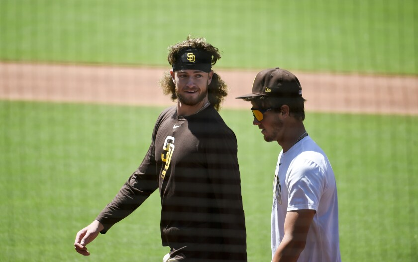Chris Paddack (left) and Wil Myers talk on the field during the Padres first workout of summer camp.