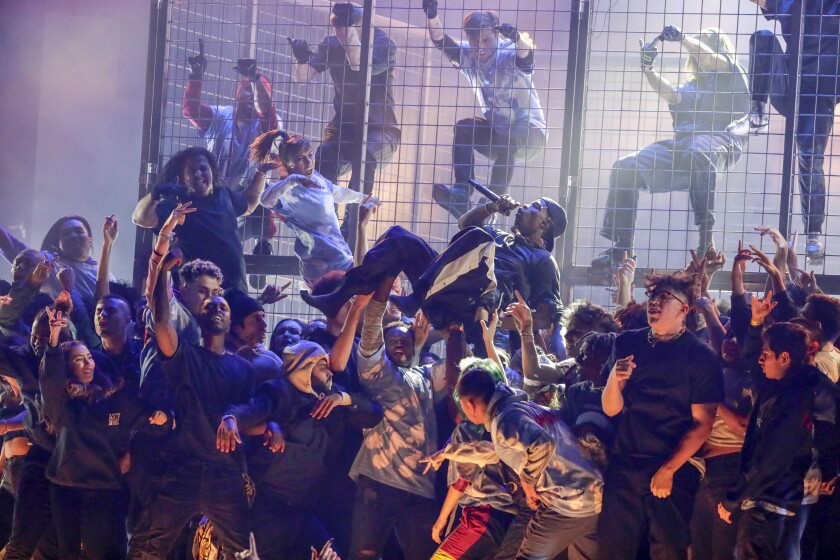 Travis Scott performs at the 61st Grammys surrounded by people, some in a cage behind him.