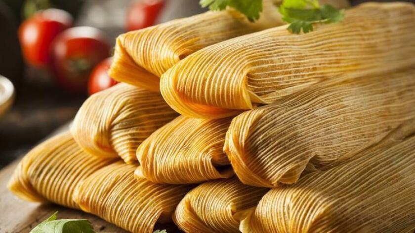 Tamales on a wooden board.