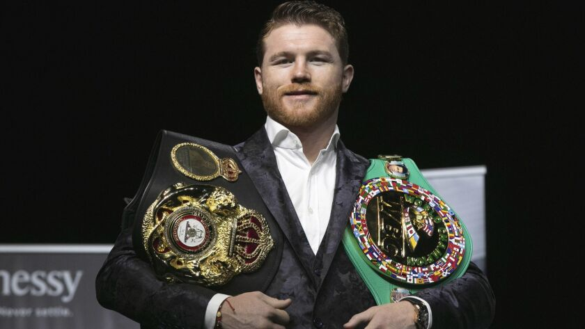 Canelo Alvarez poses for photos with his two championship belts at Madison Square Garden.