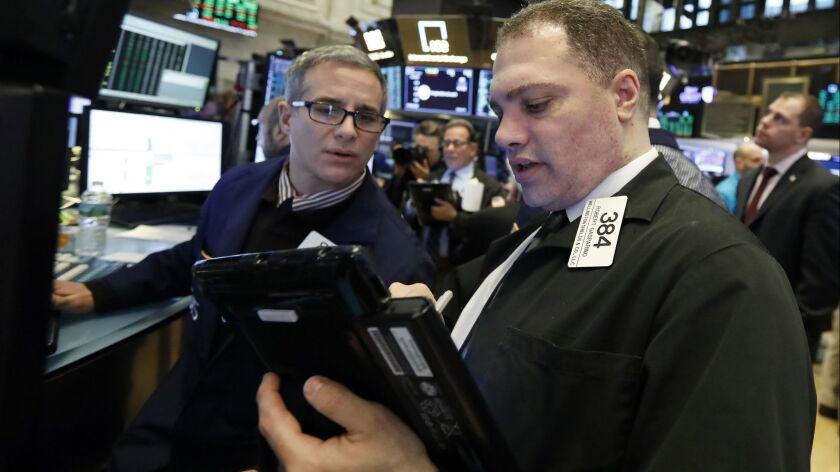 Specialist Anthony Rinaldi, left, and trader Robert Gasparino work on the floor of the New York Stock Exchange on Jan. 18.