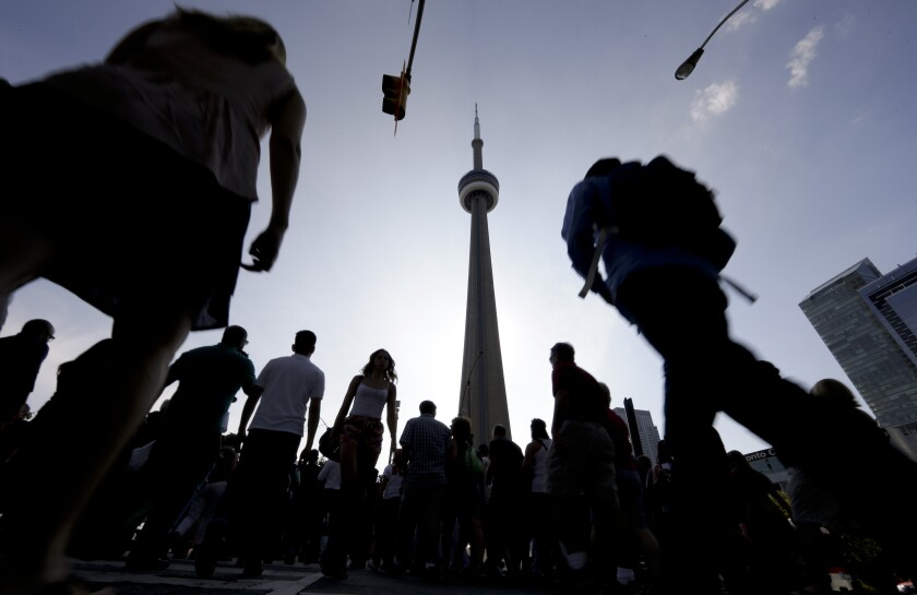 People make their way towards the CN Tower and Rogers Center in Toronto