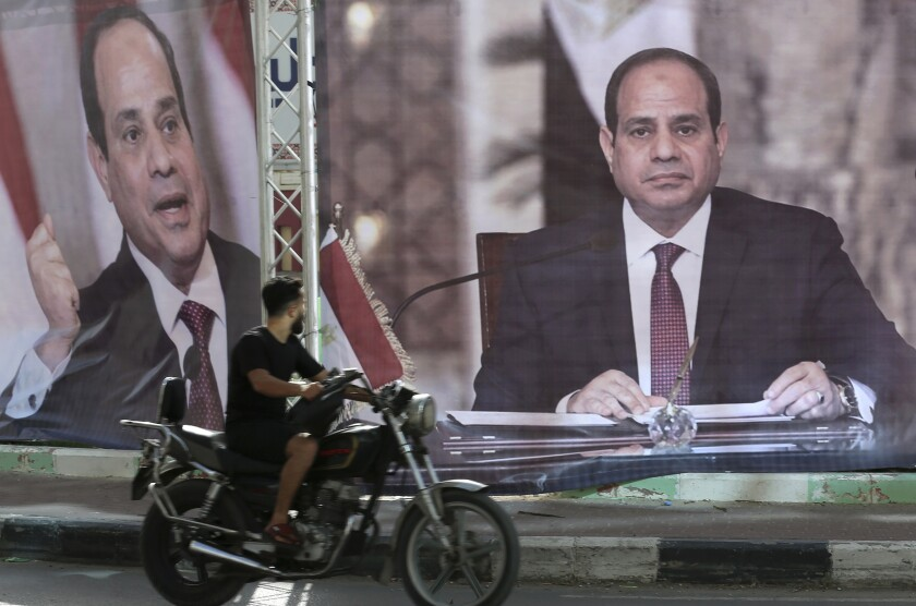 A motorcyclist passes large posters of Egyptian President Abdel Fattah Sisi displayed in Gaza City.