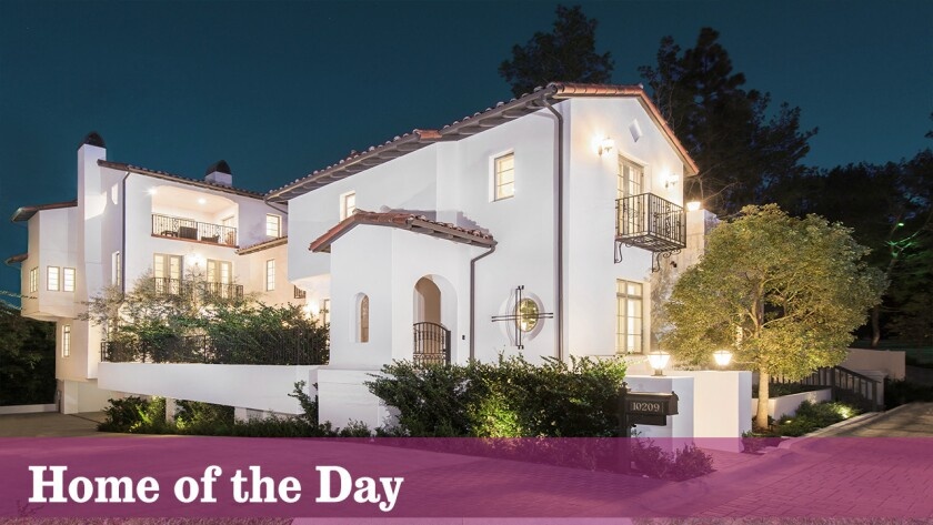 This classic, Mediterranean-style home features a portico entry, wrought-iron balconies, a red tile roof and French doors opening onto a central courtyard.