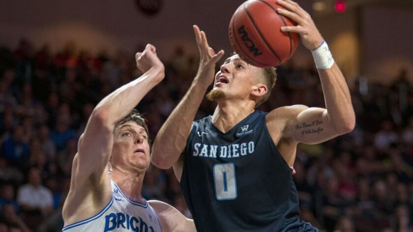 San Diego's Isaiah Pineiro (0) drives past BYU's Dalton Nixon (33) on the way to the basket during t