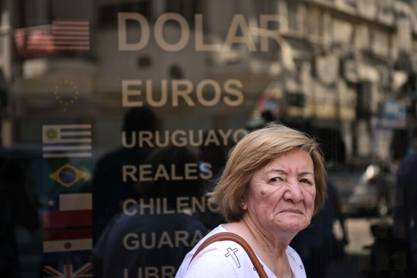 A pedestrian walks past a closed money-changing business in downtown Buenos Aires on Dec. 16, the date the new center-right government abolished the subsidized exchange rate for the Argentine peso.