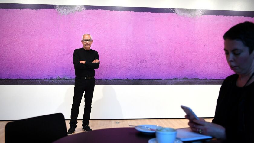 Photographer Anthony Hernandez pauses before one of his images during his solo exhibition at the San Francisco Museum of Modern Art in 2016.