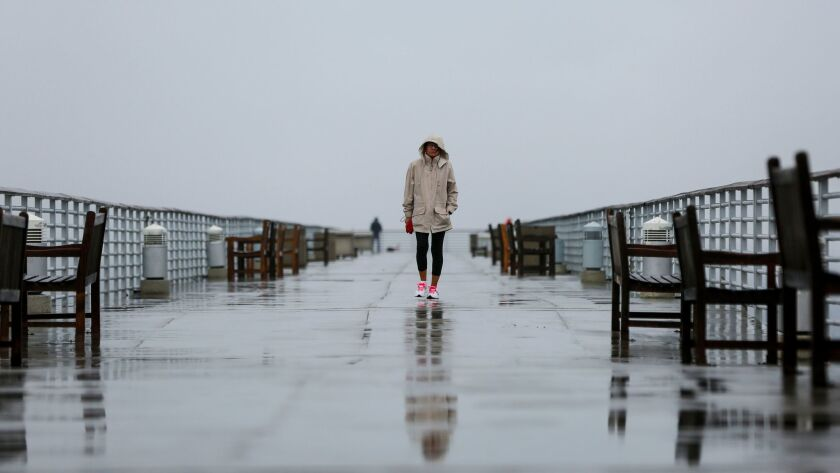 A woman walks along the Hermosa Beach Pier last week during a lingering rainstorm.