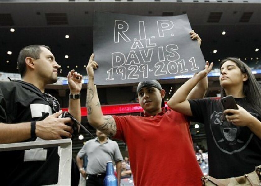 Mando Blancas, left, Luis Gonzalez, center, and Jackie Blancas hold up a sign for Oakland Raiders owner Al Davis before the NFL football game between the Oakland Raiders and the Houston Texans, Sunday, Oct. 9, 2011, in Houston. Davis died Saturday, at age 82. (AP Photo/Gerald Herbert)