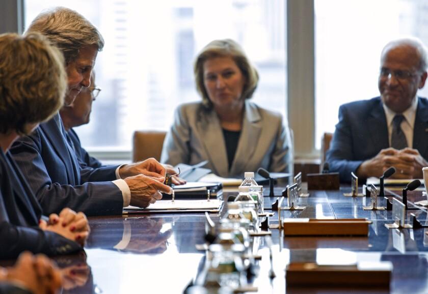Palestinian negotiator Saeb Erekat, right, talks with U.S. Secretary of State John F. Kerry, left, and Israeli negotiator Tzipi Livni at the United Nations in New York.