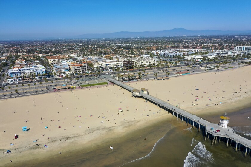 Beachgoers dot the sand in an aerial view of Huntington Beach and the pier.