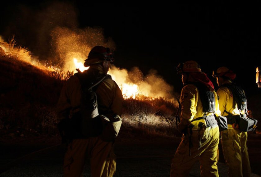 Firefighters take a stand in Twin Pines as the Silver Fire makes a push towards the road late in the evening.
