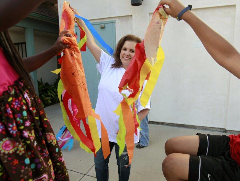 San Diego Center for Children volunteer art teacher Doreen Schonbrun leads a class in kite-making.