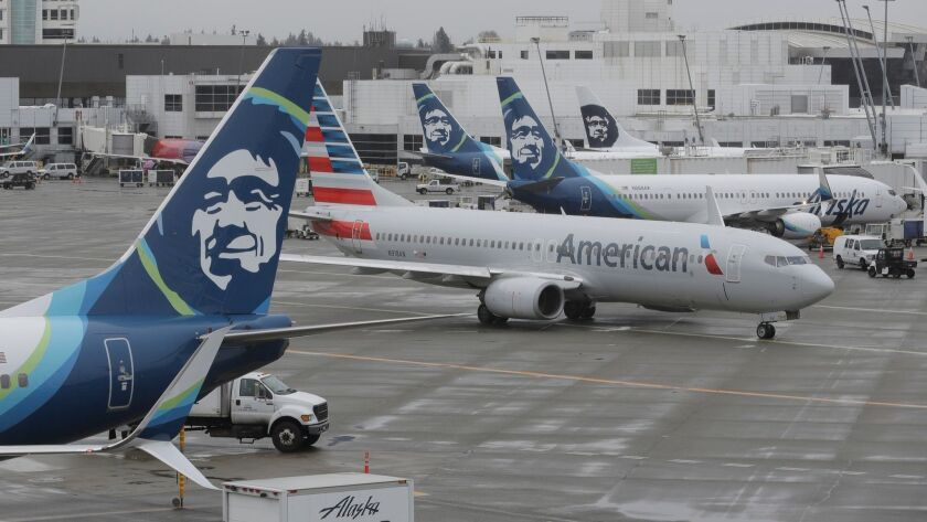 An American Airlines plane taxis past parked Alaska Airlines airplanes, Friday, April 13, 2018, at t