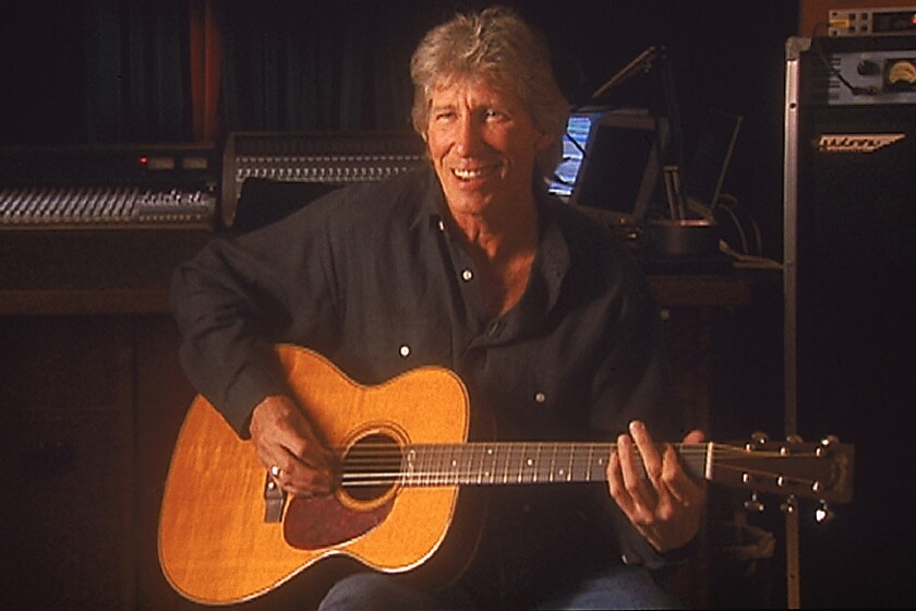 """Roger Waters playing acoustic guitar in """"Classic Albums Pink Floyd - Dark Side of the Moon"""" on PBS."""