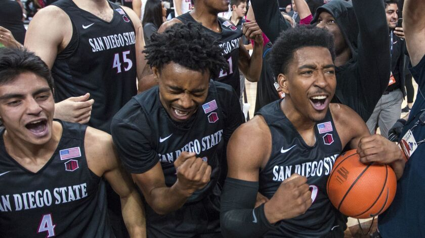 Aztecs players, including Jeremy Hemsley, center, and Devin Watson, right, celebrate an 82-75 win over New Mexico on March 10, 2018, in the final of the Mountain West tournament.