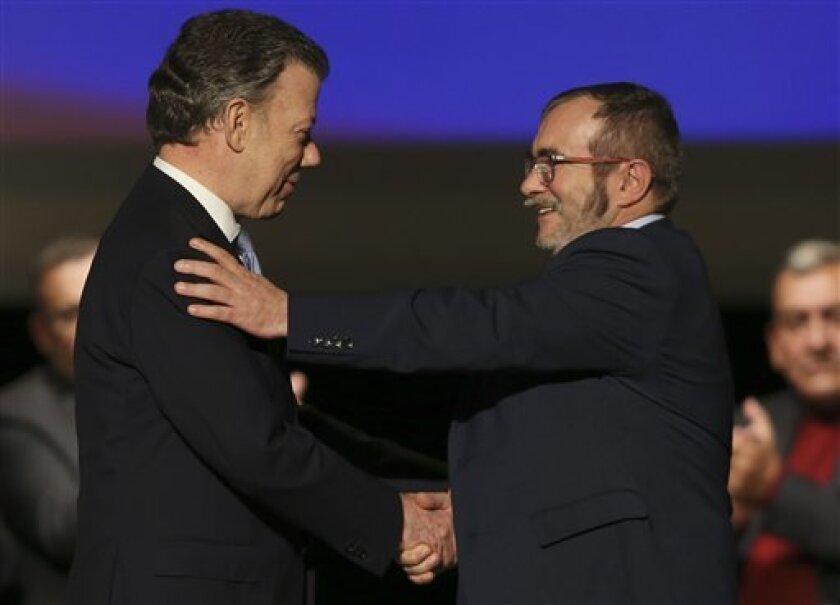 """El presidente de Colombia Juan Manuel Santos estrecha la mano de Rodrigo Londoño, conocido como """"Timochenko"""" y líder de las Fuerzas Armadas Revolucionarias de Colombia (FARC) tras firmar un nuevo acuerdo de paz en el Teatro Colón de Bogotá, el jueves 24 de noviembre de 2016."""