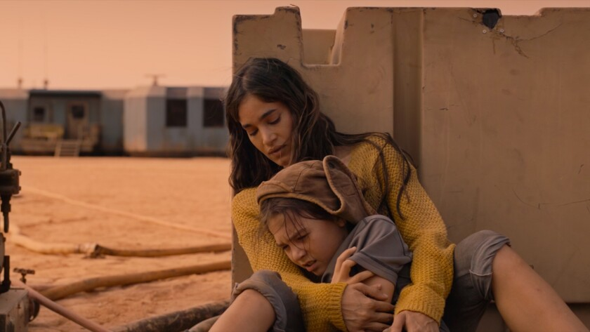 """A mother holds her young daughter in the movie """"Settlers"""""""