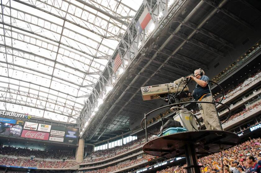 A CBS cameraman works during an NFL game in Houston in 2011. The upcoming start of the regular football season is believed to have pushed CBS and Time Warner Cable to settle their contract dispute.