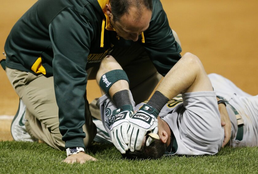 Oakland Athletics' Craig Gentry is attend to by a member of the A's medical staff after colliding with Chicago White Sox first baseman Jose Abreu during the fifth inning of a baseball game Tuesday, Sept. 9, 2014, in Chicago. (AP Photo/Charles Rex Arbogast)