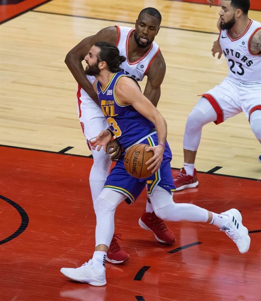 Ricky Rubio (frente) de los Jazz, controla el balón ante Serge Ibaka de los Raptors en el partido de la NBA que ambos equipos han disputado este 1 de enero en Toronto, Canadá. EFE